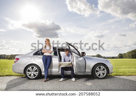 Full length of young woman looking away while man reading map in car at countryside - stock photo