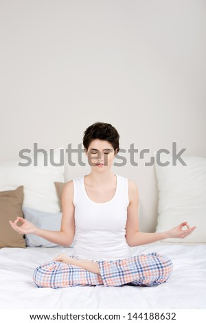 Full length of young woman meditating in lotus position on bed - stock photo
