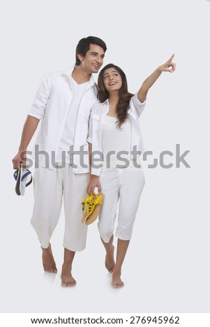 Full length of young woman showing something to man isolated on white background - stock photo