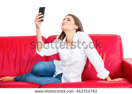 Full length of young woman taking selfie. Beautiful female is puckering while holding smart phone. She is sitting on red sofa isolated over white background.
