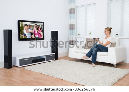Full length of young woman watching television while sitting on sofa in living room - stock photo