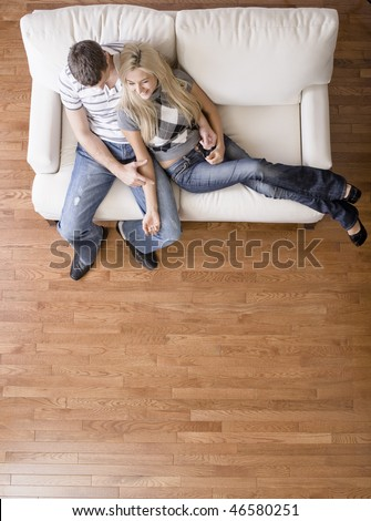 Full length overhead view of affectionate couple sitting together on white love seat. Vertical format.