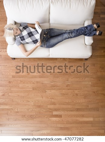 Full length overhead view of woman reclining and reading on white couch. Vertical format.