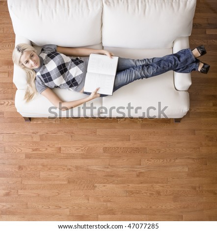 Full length overhead view of woman reclining on white couch with a book, as she looks up at the camera. Square format. - stock photo