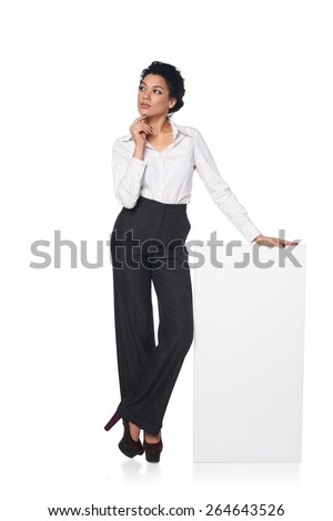 Full length pensive business woman standing leaning at blank white board, looking away, isolated on white background - stock photo