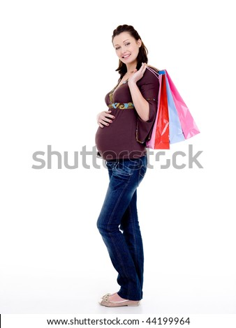 Full-length photo of a Beautiful cheerful pregnant woman with shopping bags - stock photo