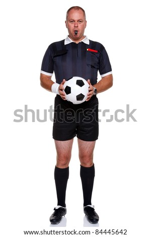 Full length photo of a football or soccer referee holding a ball with a whistle in his mouth, isolated on a white background. - stock photo