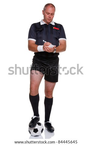 Full length photo of a football or soccer referee with ball writing in his report book, isolated on a white background. - stock photo
