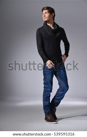 full length photo of a young casual man in jeans walking in studio -light background