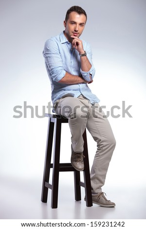 full length photo of a young casual man sitting on a chair and touching his chin while looking pensively at the camera. on gray background - stock photo