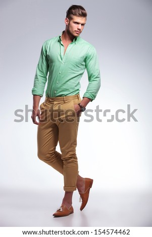 full length photo of a young casual man with a hand in his pocket, looking into the camera. on light gray background - stock photo