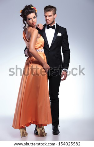 full length photo of a young fashion couple embracing with man looking at woman while she looks away, over her shoulder. on gray background - stock photo