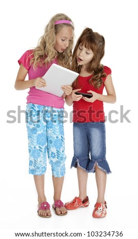 Full length photo of two little girls standing, holding tablet and smart phone, isolated on white. - stock photo