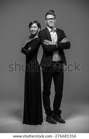 Full length photo of young  smiling couple dressed in formal clothing posing in the studio. Black and white fashion photo. - stock photo
