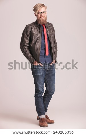 Full length picture of a casual fashion man smiling at the camera while holding both hands in his pocket. - stock photo