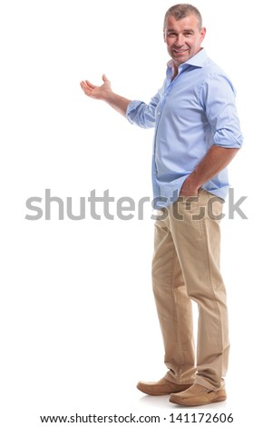 full length picture of a casual senior man presenting something in the back, with a hand in his pocket while looking at the camera. isolated on white background - stock photo