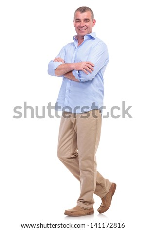 full length picture of a casual senior man standing with arms folded and looking at the camera. isolated on white background