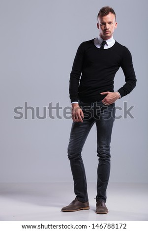 full length picture of a casual young man standing with a hand in his pocket and looking at the camera. on light gray studio background - stock photo