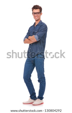 full length picture of a casual young man standing with his hands crossed and smiling to the camera. isolated on a white background - stock photo