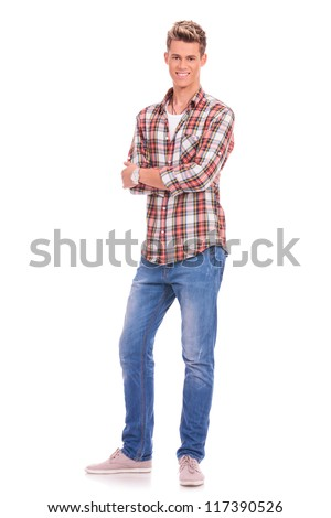 full length picture of a casual young man standing with his hands folded on white background - stock photo