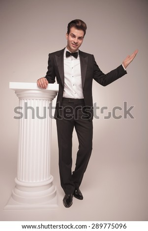 Full length picture of a handsome elegant business man holding his hand on a white column while welcoming you. - stock photo