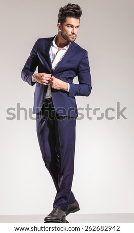 Full length picture of a handsome young business man closing his coat while looking away from the camera. - stock photo