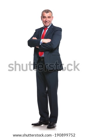 full length picture of a mid aged business man smiling with his arms crossed. isolated on a white background - stock photo