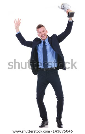 full length picture of a young business man cheering while holding a trophy in his hand. on white background