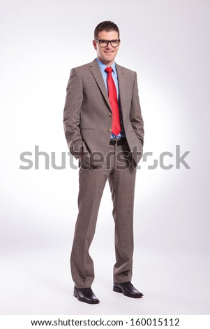 full length picture of a young business man smiling while holding both hands in pockets. on a gray background
