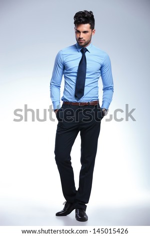 Full length picture of a young business man standing with his hand in