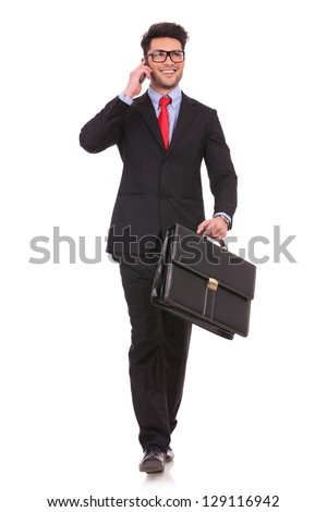 full length picture of a young business man walking forward with a briefcase in one of his hands and talking at the phone while looking away from the camera on white background - stock photo