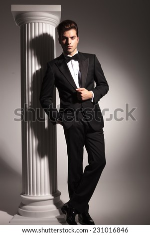Full length picture of a young bususiness man posing in studio background near a white column. - stock photo