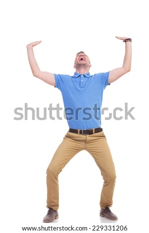 full length picture of a young casual man holding something imaginary above him with both hands and screaming out of difficulty. casual man being crushed. isolated on a white background - stock photo
