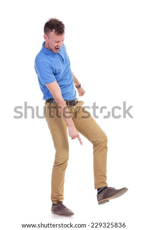full length picture of a young casual man pointing angrily at the ground while holding his foot raised, on the point of stepping on something. isolated on a white background - stock photo