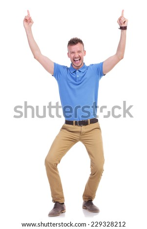 full length picture of a young casual man pointing upward with both hands while smiling for the camera with his mouth open. isolated on a white background - stock photo