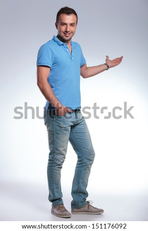 full length picture of a young casual man presenting something in the back while holding a hand in his pocket and smiling for the camera. on gray background - stock photo