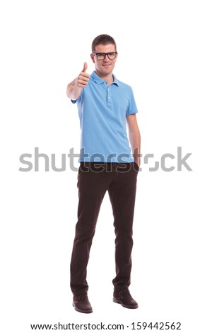 full length picture of a young casual man showing the thumb up gesture while holding a hand in his pocket. on white background