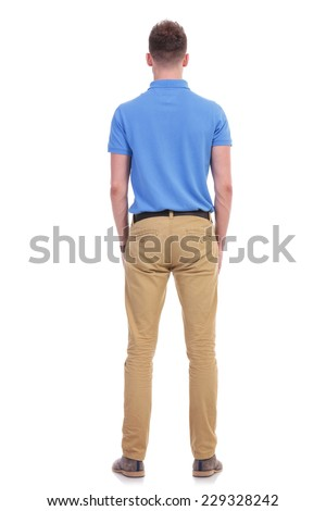full length picture of a young casual man standing with his back at the camera. isolated on a white background - stock photo