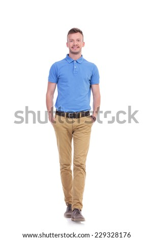 full length picture of a young casual man walking toward the camera with his hands in his pockets while smiling. isolated on a white background - stock photo