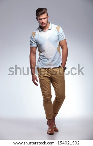 full length picture of a young casual man walking with a hand in his pocket while looking into the camera. on gray background - stock photo