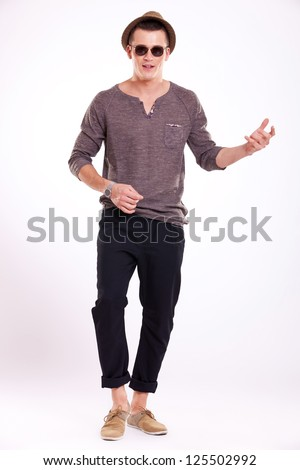 full length picture of a young casual man wearing sunglasses and a trilby hat playing at an imaginary guitar - stock photo