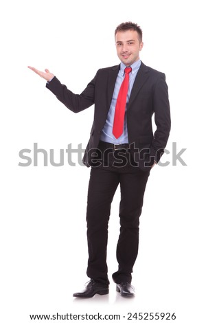 Full length picture of a young handsome business man presenting something to his right. - stock photo