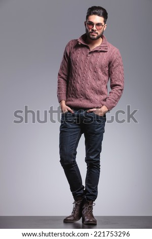 Full length picture of an young fashion man wearing sunglasses, holding his hands in pocket. On grey studio background. - stock photo