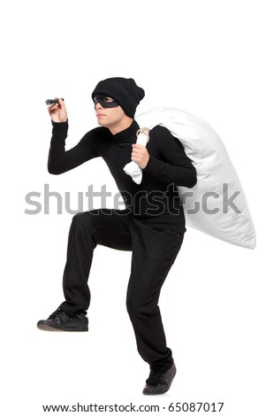 Full length portait of a robber with a bag and flashlight in hands isolated against white background - stock photo