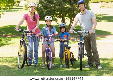 Full length portrait a family of four with bicycles in the park - stock photo