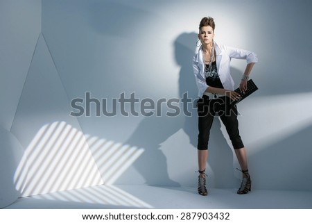 Full length portrait fashion model holding purse posing on light background - stock photo