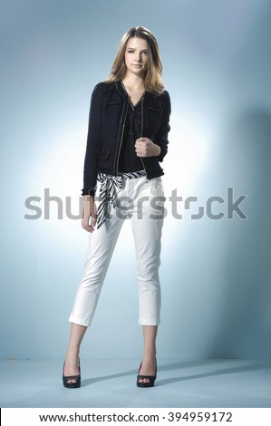 Full length portrait fashion model standing posing on light background - stock photo