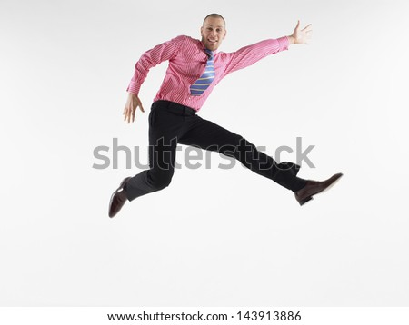 Full length portrait of a bald businessman jumping against white background - stock photo