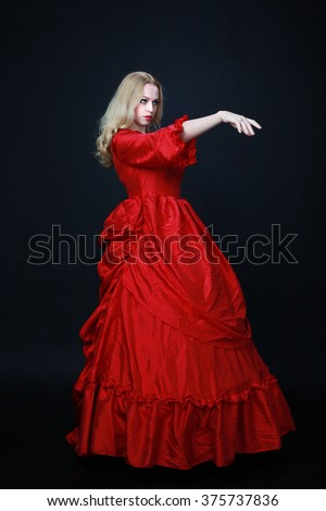 full length portrait of a beautiful blonde woman wearing a historical red silk, victorian era ball gown.