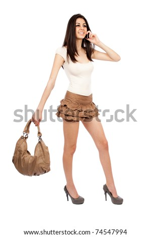 Full length portrait of a beautiful hispanic woman with a purse speaking on cellphone - stock photo